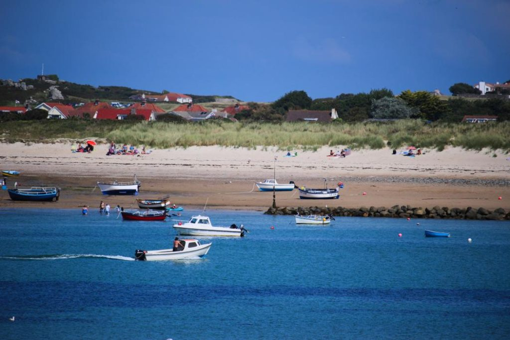 View across a bay with boats moored and sunbathers on the beach.