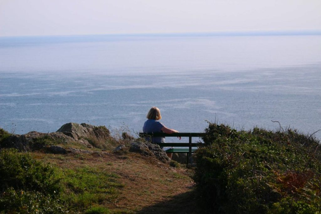 A person sitting on a bench seat on the cliff top and looking out to sea
