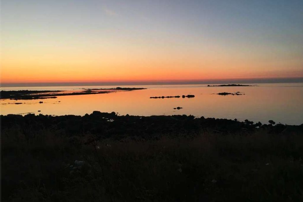 Sunset with the sun having dipped below the horizon and the cloudless sky displaying hues of orange and red, reflected in the calm sea